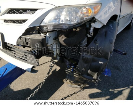 Car got severely damaged after having a collision on a freeway; preparing to get towed by a truck #1465037096