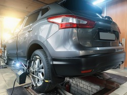 Car in auto service. Sensors on SUV wheels check alignment camber toe. Work with chassis and suspension of car