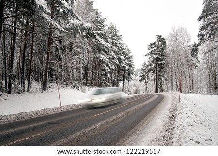 Car in blurred motion on country road in winter