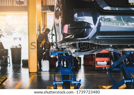car in for service mot replacing wheel and repairment, in vehicle work shop with suspension, tools and equipment fixing broken parts, concept of repair, auto mechanic shop and car external interior Photo stock ©