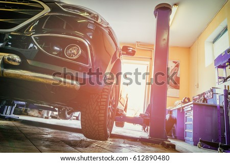 Car in garage of auto repair service shop with special repairing equipment #612890480