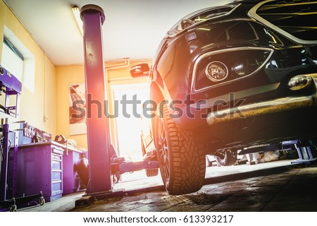 Car in garage of auto repair service shop with special repairing equipment #613393217