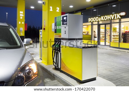 Car in gas station. Fuel, petrol dispenser, pump, handles and pillars. Fueling. Estonia. Lighted window of convenience store and coffe shop.