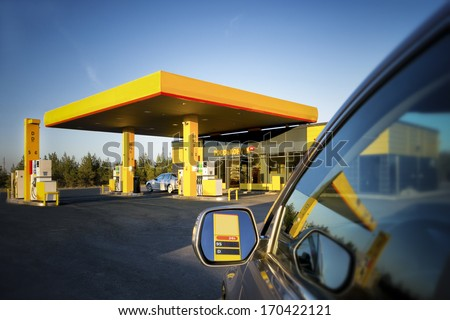 Car in gas station. Reflection on motor vehicle mirror and glass. Convenience store in Estonia