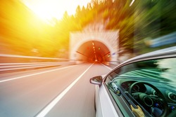 Car in motion blur driving in a tunnel at Italian mountains