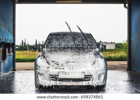 Car in outdoors self-service car wash, car in foam, toned
