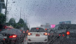 Car in rainy road with drizzle on the windshield window. Cars driving in the heavy rain and slippery road with traffic jam .Dangerous transportation and bad weather,raining blurred background