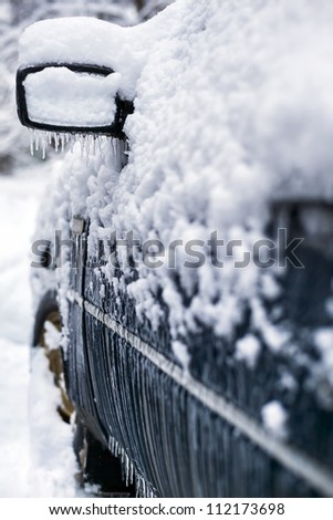 Car in snow and icicles during icing in town