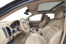 Car inside driver place. Interior of prestige modern car. Front seats with steering wheel & dashboard. Beige cockpit with metal decoration & panoramic roof on isolated white background.