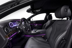 Car inside driver seat. Interior of prestige modern car. Front seat with display,steering wheel & dashboard. Black cockpit wood & metal decoration & violet ambient light on isolated white background.