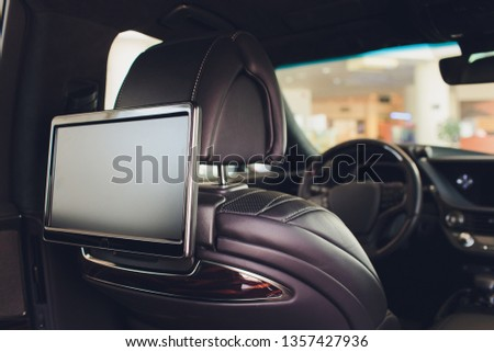 Car inside. Interior of prestige luxury modern car. Three TV displays for passenger with media control panel copy space and mock up.