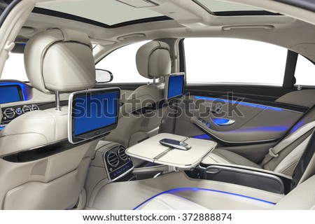 Car inside. Interior of prestige modern car. Back seats with displays, tables & mobile phone. White cockpit with panoramic roof & blue ambient light on isolated white background.