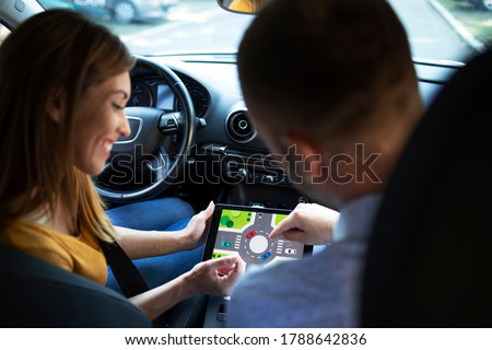 Car instructor teaching student about traffic rules on firs automobile driving class.
