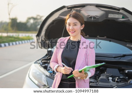 Car Insurance Agent, Young Asian saleswoman writing on clipboard with Broken car , smiling and look at the camera
