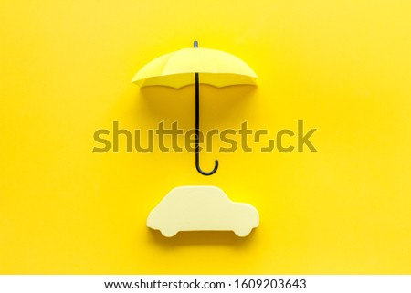 Car insurance. Automobile toy under umbrella on yellow background top-down copy space Сток-фото ©