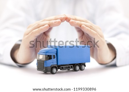 Car insurance. Blue truck miniature covered by hands.