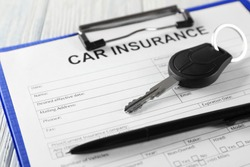 Car insurance form and key on table