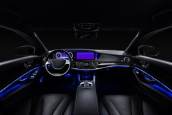 Car interior from driver seat view. Black leather cockpit with blue ambient light.