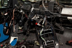 Car interior in the back of a van with a disassembled dashboard and view on shift gear and climate-control during preparation in a vehicle repair workshop. Auto service industry