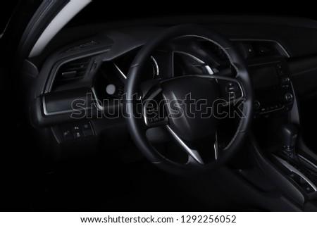 Car interior. Modern car speedometer, illuminated dashboard and steering wheel. #1292256052