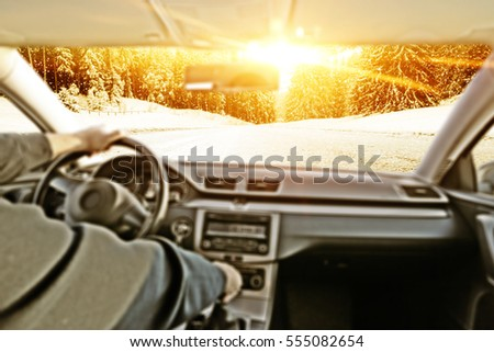 car interior with driver and winter road with snow and frost  #555082654