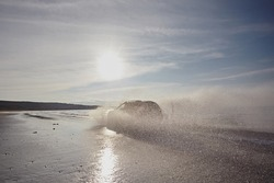 Car is driving at speed along the beach of the sea against the blue sky. From under the wheels splashed water in the form of large cloud and sun. Summer landscape