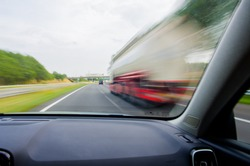 Car is going to overtake white / red truck on Dutch/European two-lane highway at high speed. Dashboard view with motion blur.