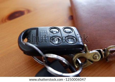 Car Key and alarm with table wood background. It is travelling time. Match with vintage, retro and classic design of blog or vlog. #1250006047
