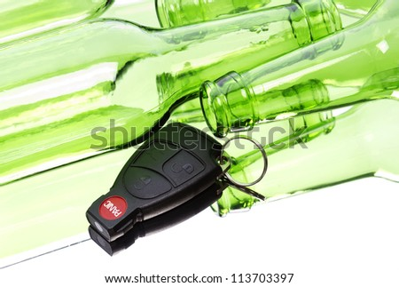 Car key and bunch of empty glass beer bottles to illustrate drunk driving concept.