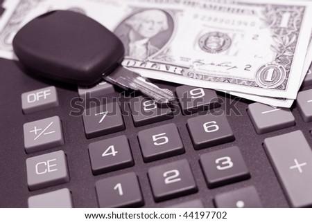 Car key and money on keypad of a calculator