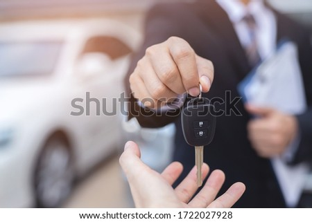 Car key, businessman handing exchange over give to the other man on showroom background. Seller dealer credit Interest payment or purchase by installment car concept.