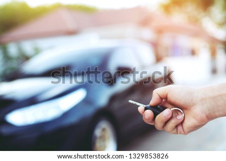 Car key in people man hand.  hand presses on the remote control car alarm systems in front of the house. Car lock #1329853826