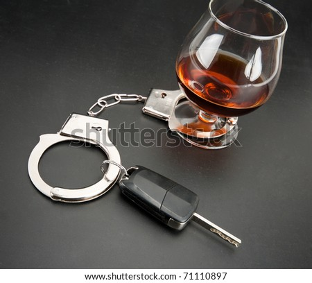 Car key locked to glass of alcohol by handcuffs - stock photo