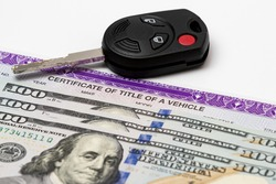 Car key, vehicle title and 100 dollar bills cash. Concept of automobile purchase, ownership, state and local taxes and fees