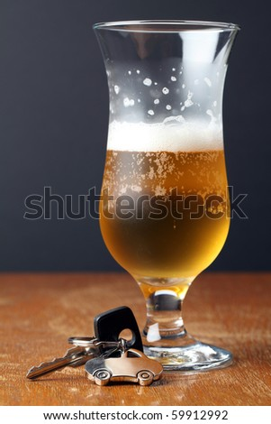 Car key with car-shaped pendant and a glass of beer. Drinking and driving concept