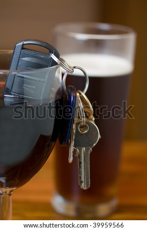 car keys in a glass of red wine shallow dof focus on the keys drink driving concept