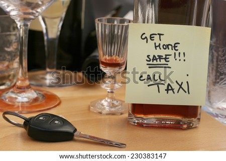 Car keys on the table full of empty glasses, bottles at party, don\'t drink and drive concept, post it note for taxi