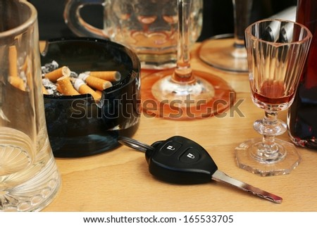 Car keys on the table full of empty glasses, bottles, full ashtray and spilled drink after a party, don\'t drink and drive concept