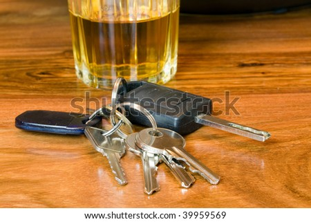 car keys with a glass of whiskey shallow dof focus on the keys