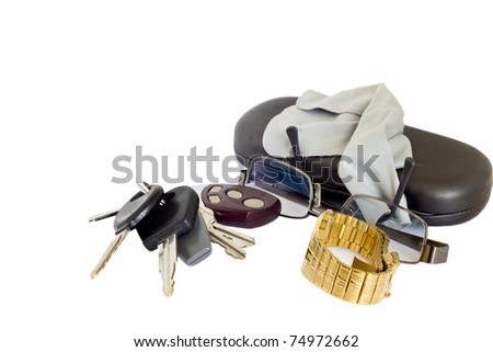Car keys with an alarm remote next to a pair of glasses, a watch and a case