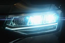 Car LED headlights in night. New modern car headlamp, close up