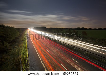 car light trails at night on motorway / highway
