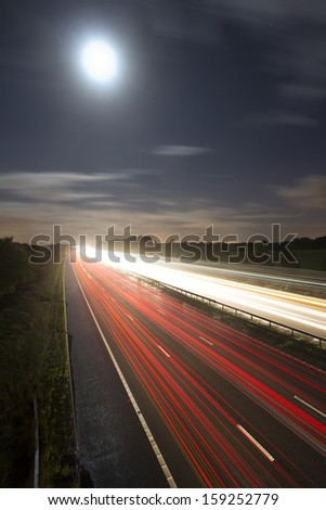 car light trails on motorway with moon