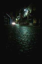 Car lights down empty dark alley at night