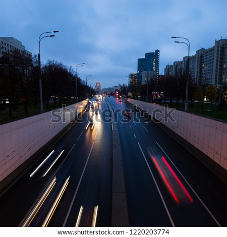 Car lights in the night city after rain. Dynamics of movement and movement in directions and road signs. #1220203774