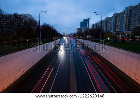 Car lights in the night city after rain. Dynamics of movement and movement in directions and road signs. #1222620148