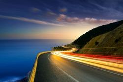 Car lights on the sea and highway. Car lights on the coastal road show the speed in traffic. Fast car lights on the road passing by the beach at sunset. Mudanya, Bursa, Turkey.