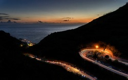 Car lighttrail following mountainroad in the night