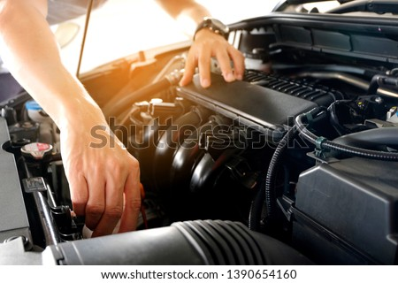 Car maintenance technician He is checking the auto engine, car inspection center. #1390654160