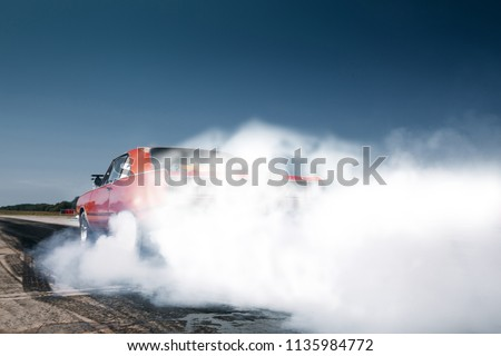 Car make tires warm up with smoke before drag race on drag strip. Burnout and warm up at the start line